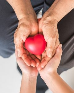 Palliative care: people holding a stylized sculptural heart.